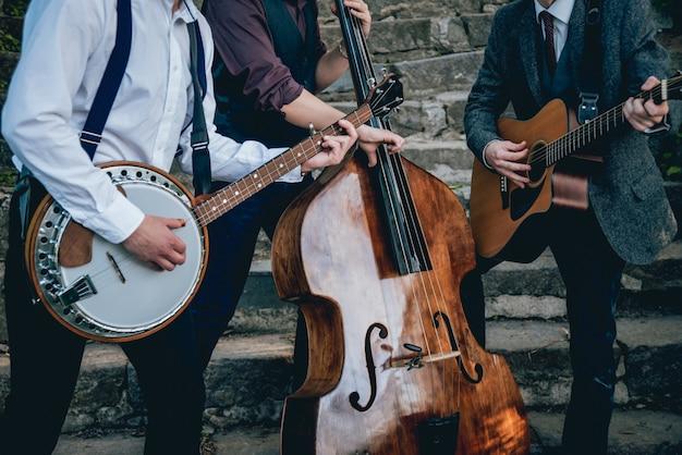 Trio van muzikanten met een gitaar, banjo en contrabas Premium Foto