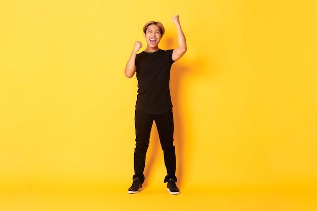 Triomfantelijke knappe aziatische man met blond haar van volle lengte, handen opsteken in de viering, ja zeggen, staande gele muur. Gratis Foto
