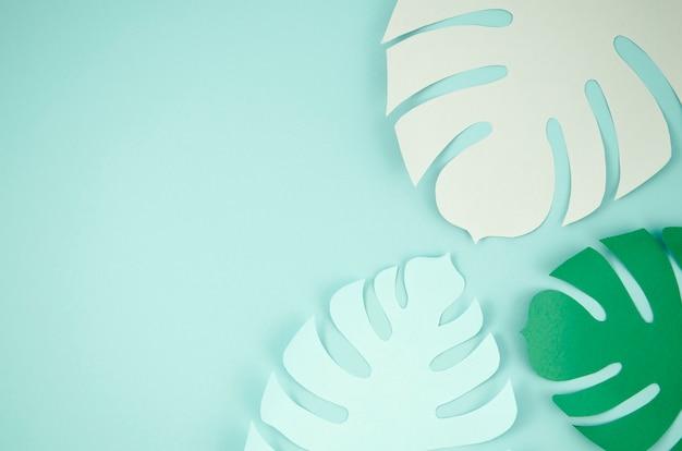 Tropische bladeren in papier gesneden stijl in blauw Gratis Foto