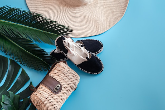 Tropische bladeren op een blauwe achtergrond met zomer accessoires. het concept van de zomervakantie. Gratis Foto