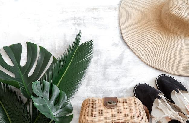 Tropische bladeren op een witte achtergrond met zomer accessoires concept van zomervakantie en recreatie. poster banner, briefkaartsjabloon. Gratis Foto