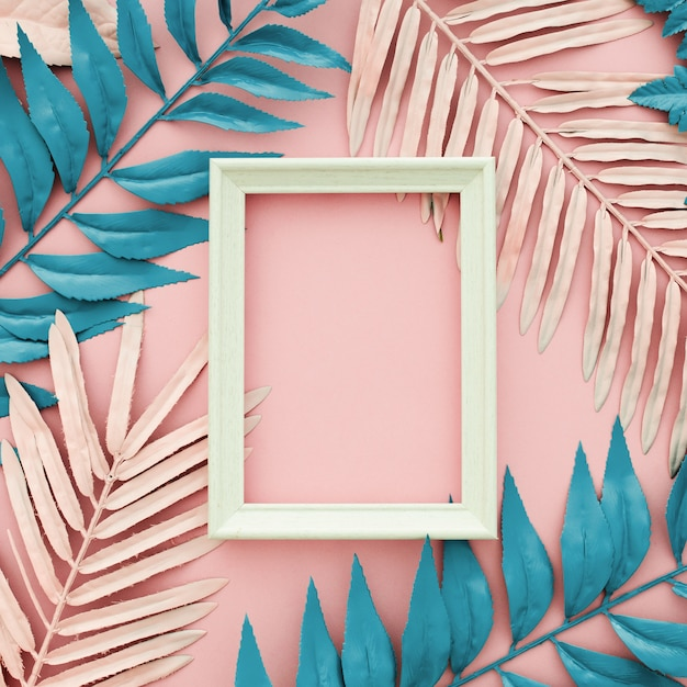 Tropische blauwe en roze palmbladen met wit kader op roze achtergrond Gratis Foto