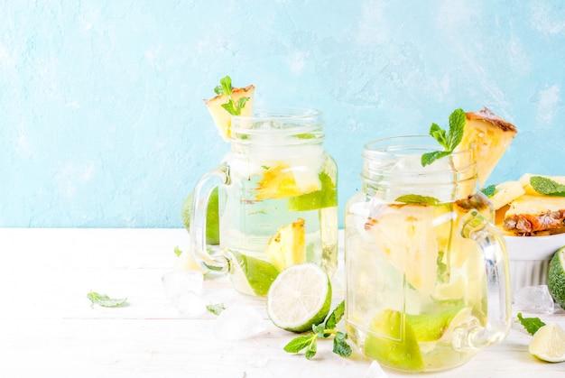 Tropische drank ananasmojito of limonade met verse limoen en mint lichtblauwe achtergrond Premium Foto