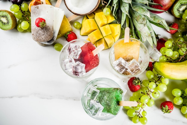 Tropische ijslollys met chiazaad en vruchtensap - ananas, sinaasappel, mango, banaan, kiwi, kokosnoot, druiven, perzik, aardbei Premium Foto