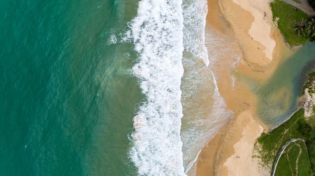 Tropische overzees en golf die op zandige kust bij karonstrand verpletteren in van de de meningshommel van phuket thailand luchtcamera top down. Premium Foto
