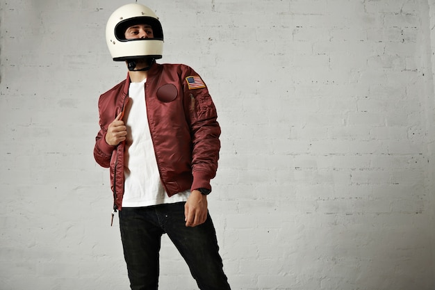 Trots uitziende motorrijder in een effen witte helm, bordeaux nylon bomberjack, jeans en t-shirt tegen witte muurachtergrond Gratis Foto