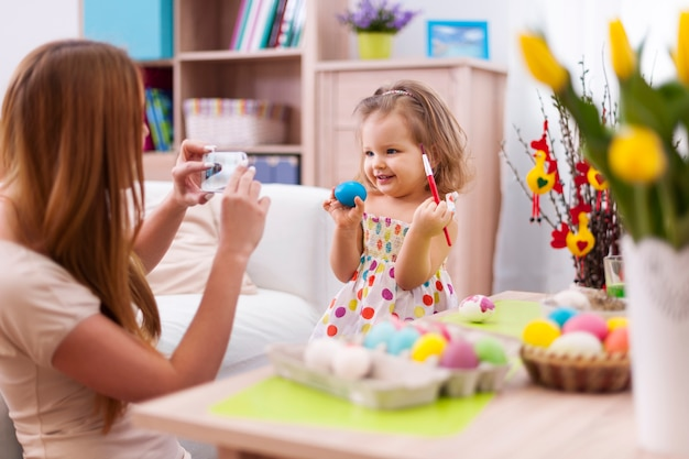 Trotse moeder maakt een foto van haar dochter met paasei Gratis Foto