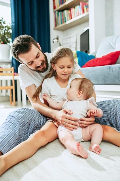 Trotse vader die zijn pasgeboren babydochter thuis houdt Gratis Foto