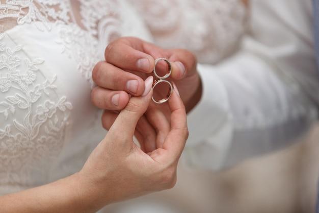 Trouwdag. bruiloft details close-up. twee gouden trouwringen in de handen van de pasgetrouwden met ruimte. net getrouwd Premium Foto