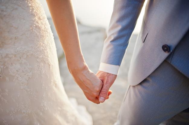 Trouwdag. handen in handen van jonggehuwdepaar. Premium Foto