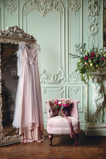 Trouwjurk en bruidsboeket in een prachtig interieur Premium Foto