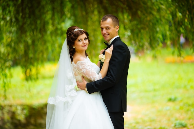 Trouwkoppel. mooie bruid en bruidegom. pas getrouwd. detailopname. gelukkige bruid en bruidegom op hun bruiloft knuffelen. bruid en bruidegom in een park. trouwjurk. bruids bruiloft, herfst Premium Foto