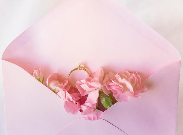 Trouwring in envelop met roze bloemen Gratis Foto