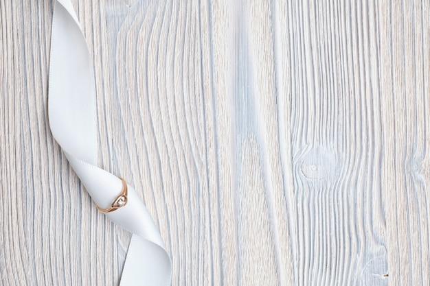 Trouwring met een wit lint op een houten achtergrond. bovenaanzicht. Premium Foto