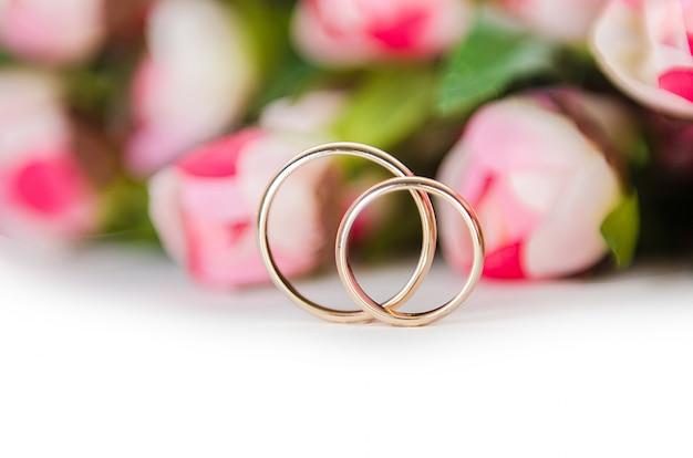 Trouwringen en bloemen op wit worden geïsoleerd dat Premium Foto