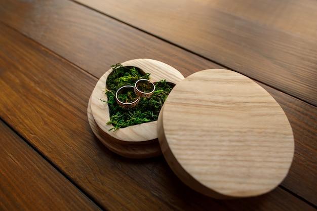 Trouwringen in ringsdoos in vorm van hart met groen mos op houten achtergrond met exemplaarruimte. rustieke bruiloft concept. Premium Foto