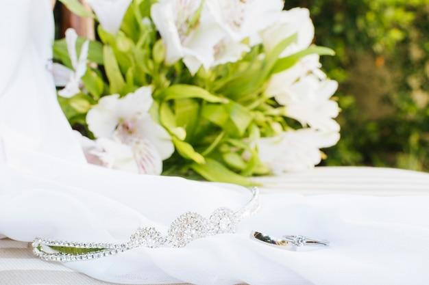 Trouwringen; kroon; sjaal in de buurt van het bloemboeket op tafel Gratis Foto