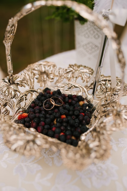 Trouwringen liggen in een mand met bessen - bosbessen, voor een veldopname van de pasgetrouwden, rustieke bruiloft, selectieve aandacht Premium Foto