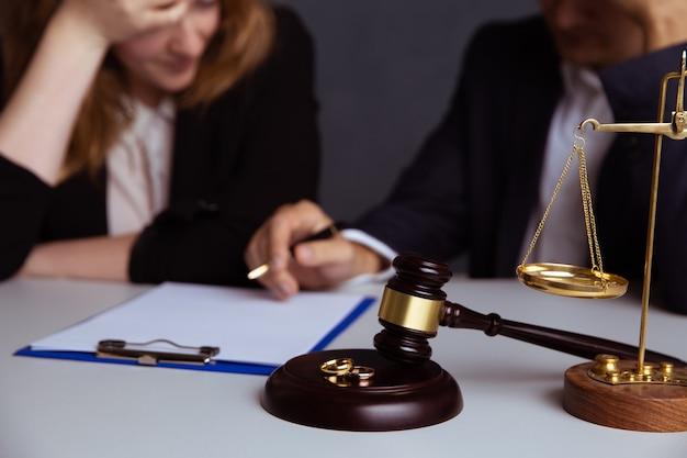 Trouwringen op een houten bord en rechter hamer met echtpaar scheiden Premium Foto