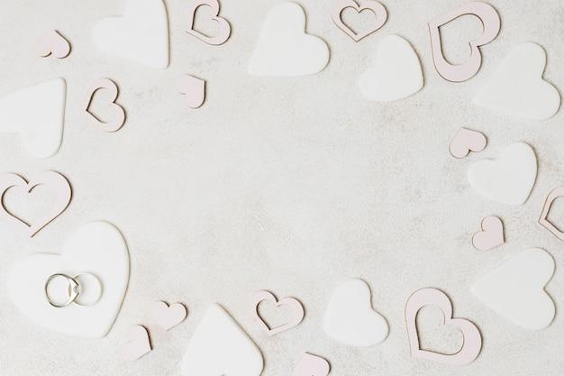 Trouwringen op witte hartvorm over de concrete achtergrond Gratis Foto