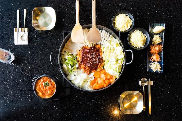 Tteok-bokki (koreaanse traditionele gerechten warme en pittige rijstwafel), combinatie en breng bladerdeeg met kaas en groente op de zwarte tafel Premium Foto