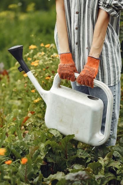 Tuinieren in de zomer. vrouw bloemen met een gieter water geven. meisje met een hoed. Gratis Foto
