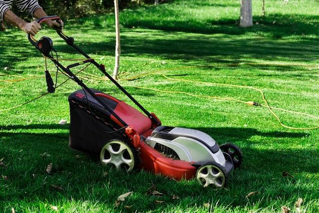 Tuinman door elektrische grasmaaier die groen gras in de tuin maait. Premium Foto