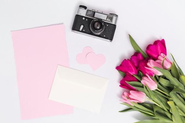 Tulp bloemen; retro camera; hart vorm; en blanco papier tegen geïsoleerde op witte achtergrond Gratis Foto