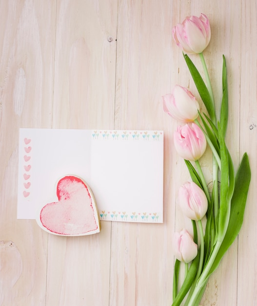 Tulpen met blanco papier en hart Gratis Foto