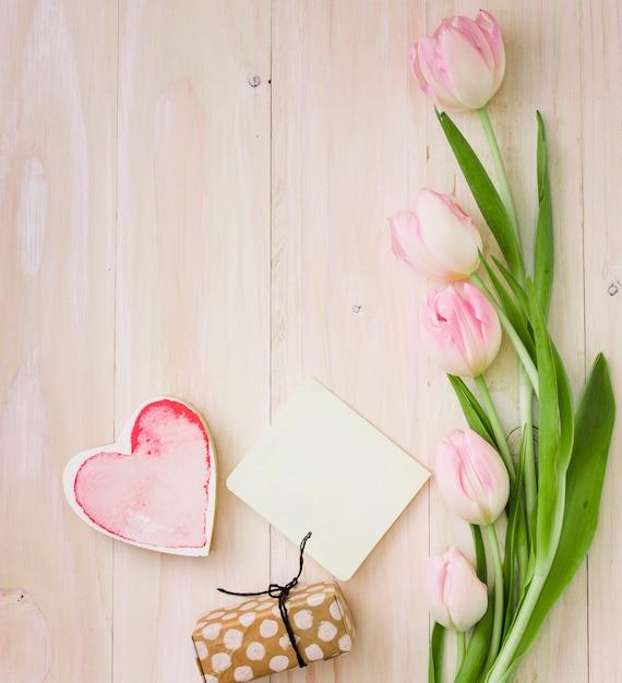 Tulpen met geschenkdoos en papier op tafel Gratis Foto