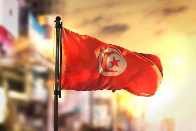 Tunesië vlag tegen stad wazige achtergrond bij zonsopgang achtergrondverlichting Premium Foto
