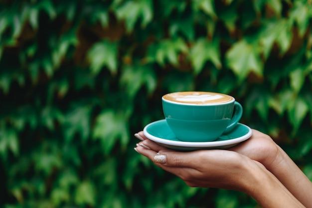 Turkoois gekleurde kop warme cappuccino in handen van de vrouw Premium Foto