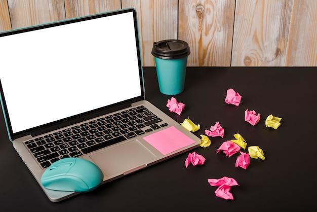Turkoois muis; zelfklevende notitie; afhaalmaaltijden; verfrommeld papier en laptop met wit scherm op zwarte achtergrond Gratis Foto