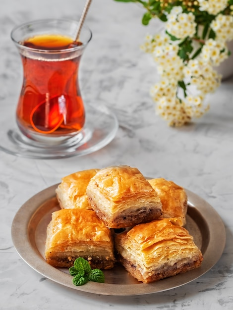 Turks dessert baklava met walnoten en hazelnoten en zwarte sterke turkse thee Premium Foto