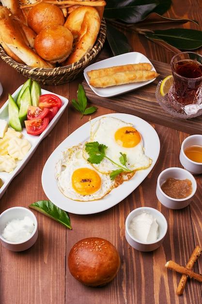 Turks ontbijt met gebakken eieren, tomaat, komkommer, kaasrassen, zwarte groene olijven, honing, jam, roomkaas, galetabrood en een glas thee Gratis Foto