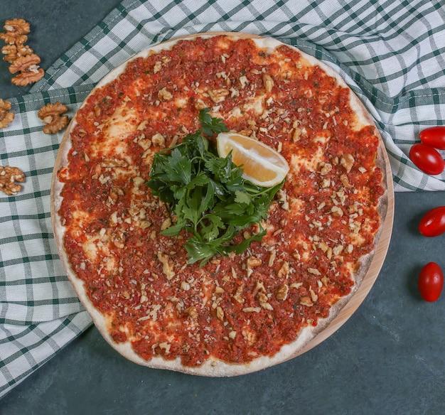 Turks straatvoedsel lahmacun met citroen en verse peterselie. Gratis Foto