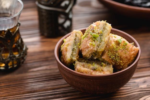 Turkse dessertbaklava met pistache in aarden kom op houten bureau Gratis Foto