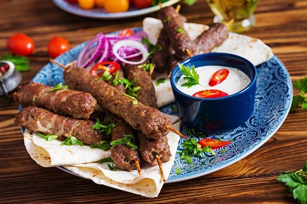 Turkse en arabische traditionele ramadan mix kebab plaat. kebab adana, kip, lam en rundvlees op lavashbrood met saus. bovenaanzicht Gratis Foto