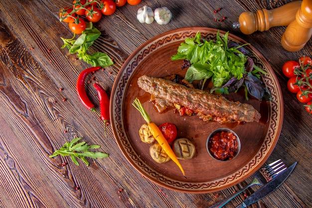 Turkse en arabische traditionele ramadanmix kebabplaat, kebablam en rundvlees met gebakken groenten, champignons en tomatensaus. bovenaanzicht, close-up Premium Foto