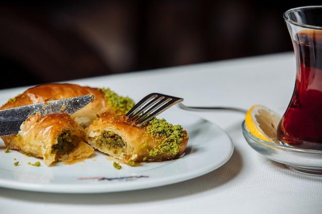 Turkse pakhlava met pistacios geserveerd met zwarte thee Gratis Foto
