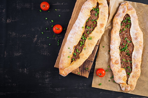 Turkse pide met gehakt, kiymali pide. traditionele turkse keuken. turkse pizza pita met vlees. bovenaanzicht, boven het hoofd Premium Foto
