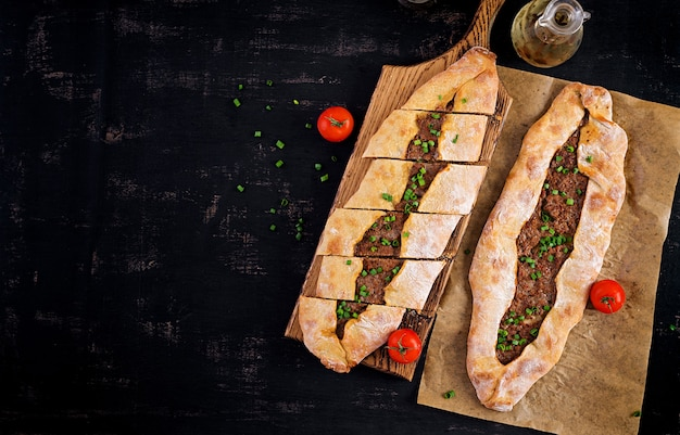 Turkse pide met gehakt, kiymali pide. traditionele turkse keuken. turkse pizza pita met vlees. bovenaanzicht, boven het hoofd Gratis Foto
