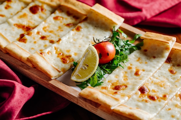 Turkse pide met gesmolten kaas, tomaat, citroen en gehakte peterselie. Gratis Foto