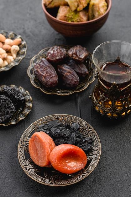 Turkse thee met dadels en gedroogde abrikoos; rozijn in een arabische ijzeren plaat voor ramadan Gratis Foto