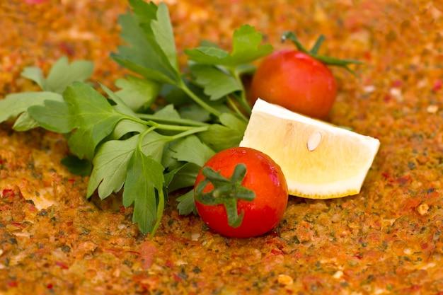 Turkse tortilla pita met gehakt en kruiden, met cherrytomaatjes en peterselie bladeren. Premium Foto