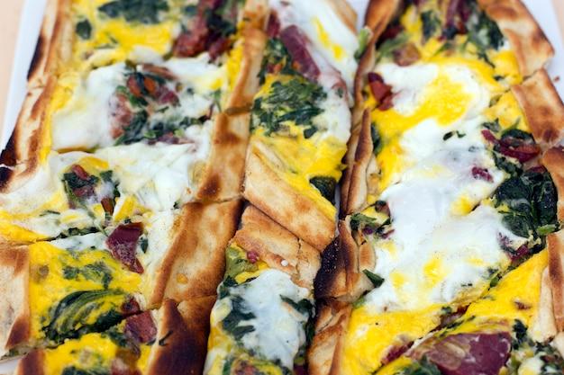 Turkse tortilla pita met spekweefsel, eieren en groene kruiden. Premium Foto