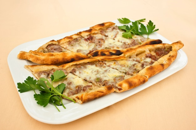 Turkse tortilla pita met stukjes vlees, gesmolten kaas en plakjes groenten Premium Foto