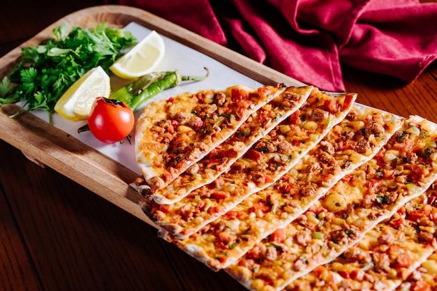 Turkse traditionele lahmacun met groene salade, citroen en tomaat in houten plaat. Gratis Foto