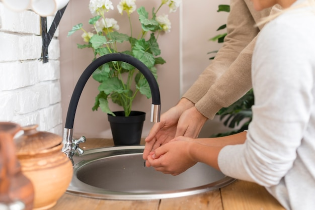 Tutor en jonge student hun handen wassen Gratis Foto