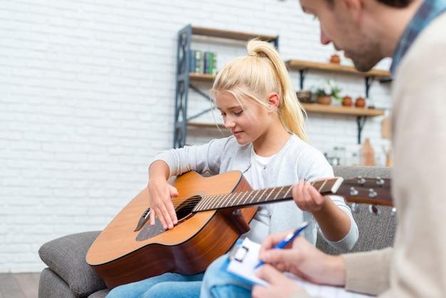 Tutor en jonge student leren gitaar spelen Gratis Foto